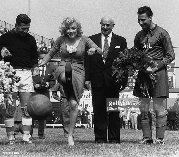 Marilyn Monroe kicks a soccer ball with Israeli goalkeeper Yaakov Hodorov standing next to her for the ceremonial kick off of a match between a...