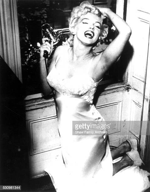 Marilyn Monroe kneels by an open window holding a hair dryer in 1954 during the filming of 'The Seven Year Itch' in New York New York