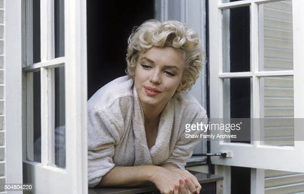 Marilyn Monroe leaning out of a window in her bathrobe in 1954 during the filming of 'The Seven Year Itch' in New York New York