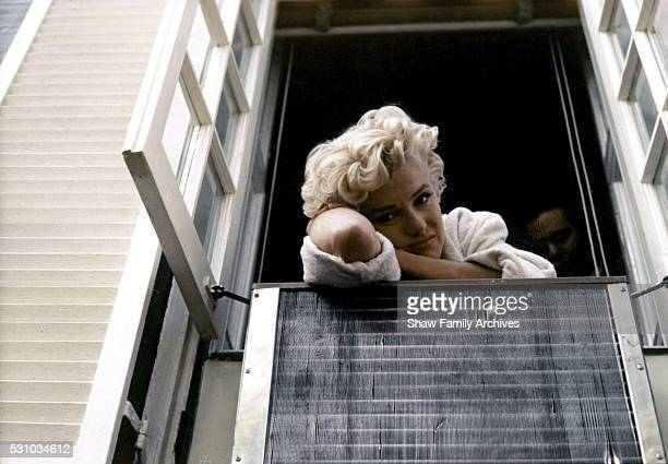 Marilyn Monroe leaning out of a window wearing a bathrobe in 1954 during the filming of The Seven Year Itch in New York New York