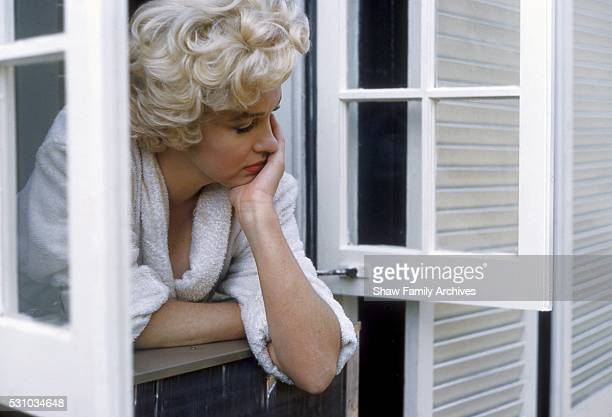 Marilyn Monroe leaning out of a window wearing a bathrobe in 1954 during the filming of 'The Seven Year Itch' in New York New York
