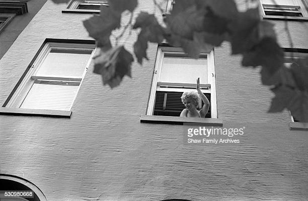 """Marilyn Monroe leans out of a window to wave in 1954 during the filming of """"The Seven Year Itch"""" in New York, New York."""