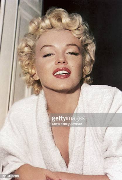 Marilyn Monroe leans out of a window wearing a bathrobe in 1954 during the filming of The Seven Year Itch in New York New York