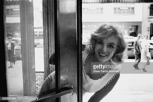Marilyn Monroe leans out of the glass door of a department store on Fifth Avenue in 1957 in New York, New York.