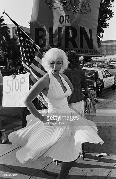 Marilyn Monroe lookalike entertains a crowd of onlookers and protesters outside the 1980 Hollywood California Adult Entertainment Awards held at the...