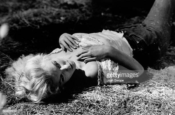 Marilyn Monroe lying alone on the ground in scene from film River of No Return