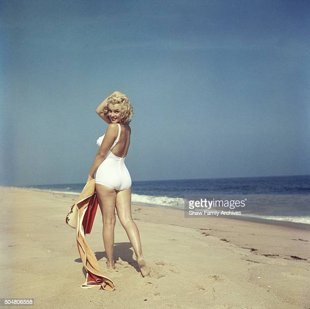 Marilyn Monroe on the beach looking back at the camera holding a towel and bag in her hand in 1957 in Amagansett New York