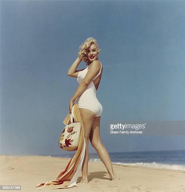 Marilyn Monroe on the beach looking back at the camera with a towel and beach bag in her hand in 1957 in Amagansett New York