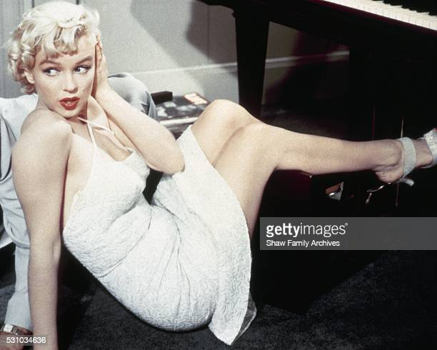 Marilyn Monroe on the floor wearing a white dress after falling off a piano stool during the filming of The Seven Year Itch in Los Angeles California