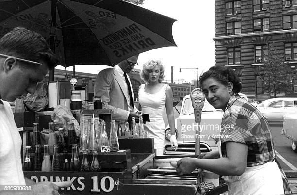 Marilyn Monroe orders a hot dog from a stand with her husband the playwright Arthur Miller in 1957 in New York New York