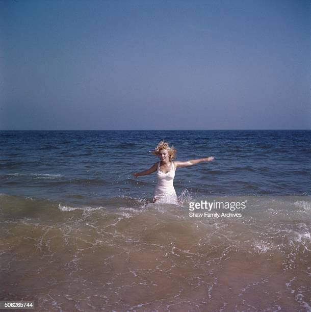 Marilyn Monroe plays in the water at the beach with her arms outstretched in 1957 in Amagansett New York