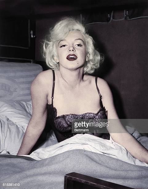 Marilyn Monroe poses in a bed wearing sexy lingerie during the shooting of her film Some Like It Hot