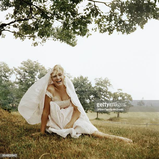 Marilyn Monroe poses sitting in the grass barefoot wearing a pink dress in 1957 in Amagansett New York