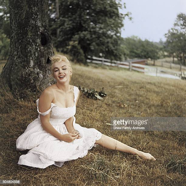 Marilyn Monroe poses sitting in the grass barefoot, wearing a pink dress in 1957 in Amagansett, New York.