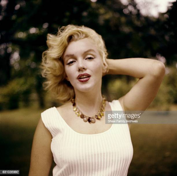 Marilyn Monroe poses wearing an amber bead necklace in 1957 in Amagansett, New York.