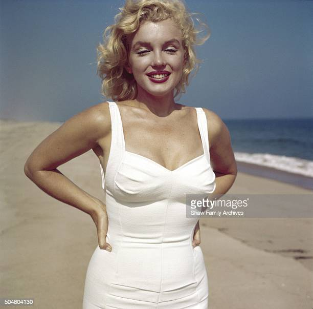 Marilyn Monroe poses with her hands on her hips on the beach in 1957 in Amagansett New York
