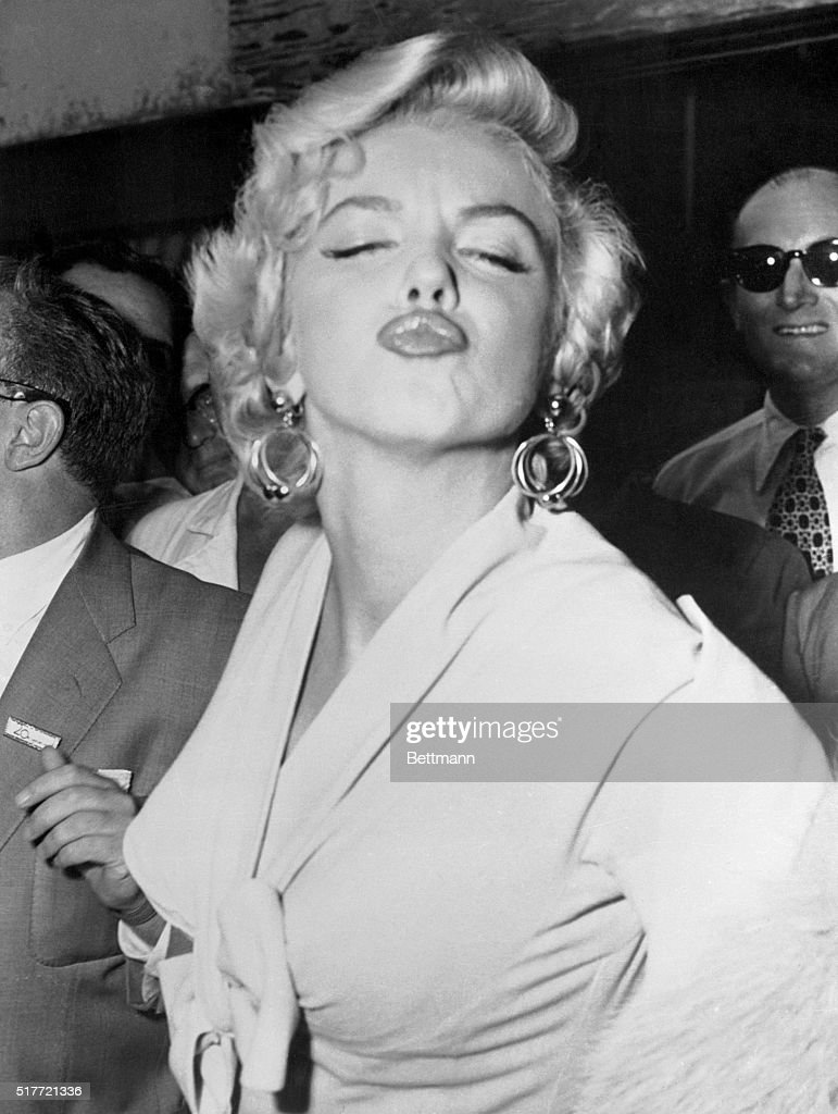 Marilyn Monroe puckers for photographers in Idlewild Airport after a cross-country flight from Los Angeles. She has arrived in New York to work on The Seven Year Itch.