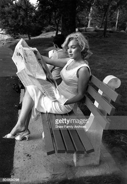 Marilyn Monroe reads a newspaper while sitting next to a man proposing to his girlfriend on a Central Park bench in 1957 in New York New York