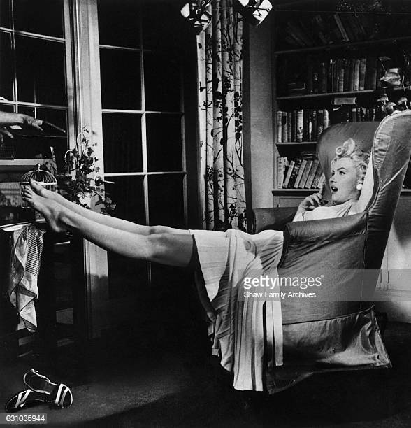 Marilyn Monroe reclines in an armchair on set during the filming of 'The Seven Year Itch' in 1954 in Los Angeles California