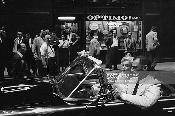 Marilyn Monroe rides in a convertible Ford Thunderbird with her husband and playwright Arthur Miller with a crowd of onlookers on the street in 1957...