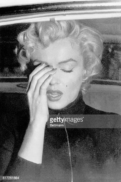 Marilyn Monroe seems to be brushing away a tear in this picture taken through a window of an automobile October 6 outside the Beverly Hills mansion...