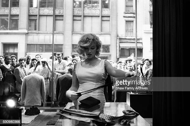 Marilyn Monroe shops in a men's clothing store on Fifth Avenue with onlookers seen through the shop windows in 1957 in New York New York