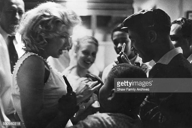 Marilyn Monroe signs autographs for a group of young fans in 1957 in New York New York
