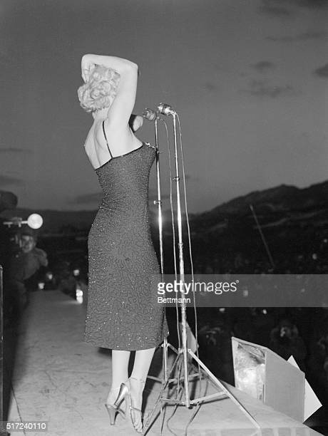 Marilyn Monroe sings a large crowd of American troops hidden by the gathering dusk in Korea
