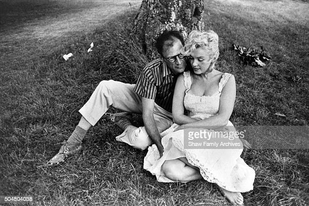 Marilyn Monroe sits barefoot in the grass wearing a dress with her husband playwright Arthur Miller in 1957 in Amagansett New York