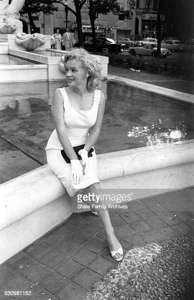 Marilyn Monroe sits in front of the fountain at the Plaza Hotel in 1957 in New York New York