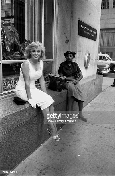 Marilyn Monroe sits on a window sill of Tiffany's in 1957 in New York New York