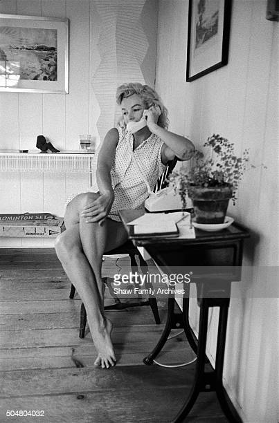 Marilyn Monroe sits with her legs crossed and her hand on one knee while talking on the telephone at her home in 1957 in Amagansett New York