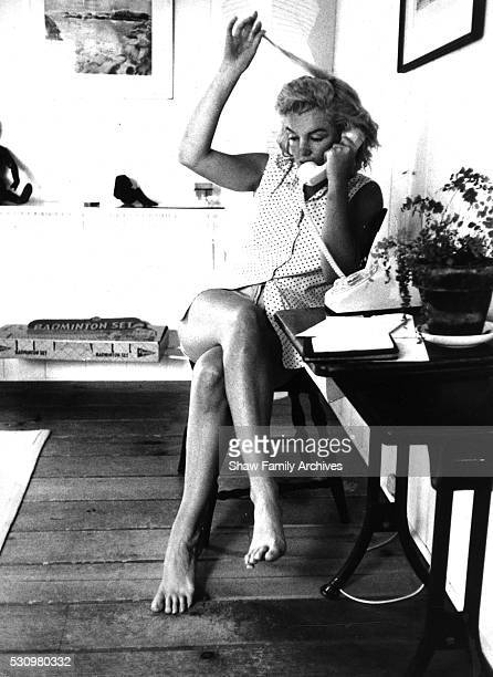 Marilyn Monroe sits with her legs crossed and plays with her hair while talking on the telephone at her home in 1957 in Amagansett New York