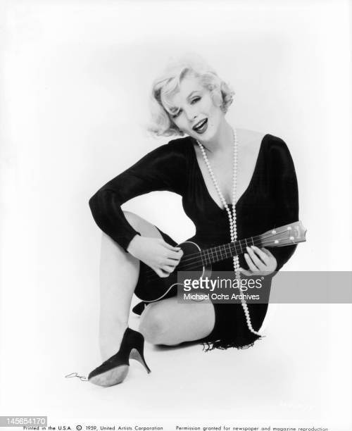 Marilyn Monroe sitting wearing a long pearl necklace and playing the ukulele in a scene from the film 'Some Like It Hot' 1959