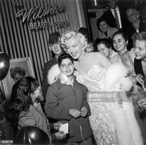 Marilyn Monroe smiles as she poses with fans in front of the Wilshire Beauty Shop at the premiere of director Jean Negulesco's film 'How to Marry a...