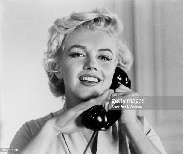 Marilyn Monroe smiles with her hand covering the receiver of a telephone in a room at the Hotel St Regis in 1954 in New York New York
