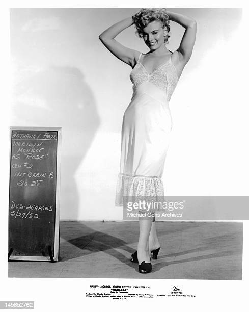 Marilyn Monroe standing next to a chalkboard in a dress slip with her arms resting on her head in a scene from the film 'Niagara' 1952