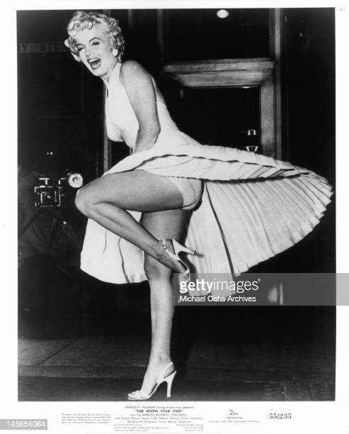 Marilyn Monroe standing on one leg on top of a vent that is blowing air up her dress as she laugh and smiles in a scene from the film 'The Seven Year...