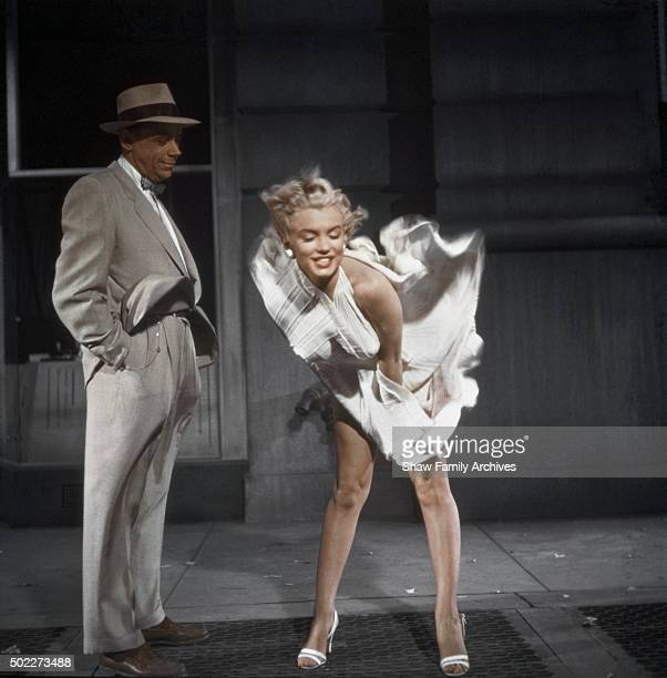 Marilyn Monroe standing over a subway grate with her white dress blowing and costar Tom Ewell looking on in 1954 during the filming of 'The Seven...