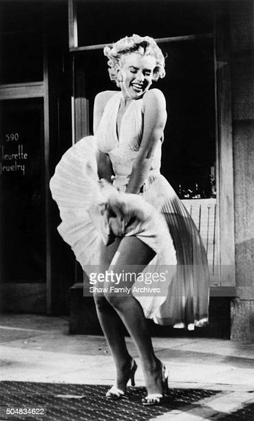 Marilyn Monroe standing over a subway grate with her white dress blowing in 1954 during the filming of The Seven Year Itch in Los Angeles California