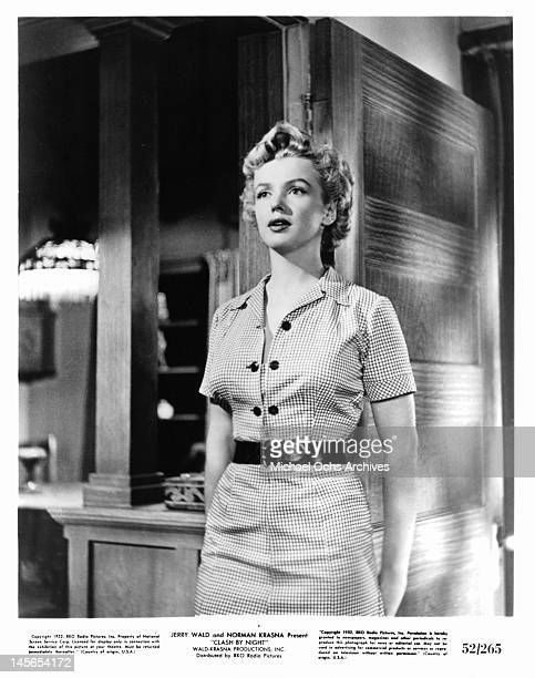 Marilyn Monroe standing wearing a checkered dress in a scene from the film 'Clash By Night' 1952