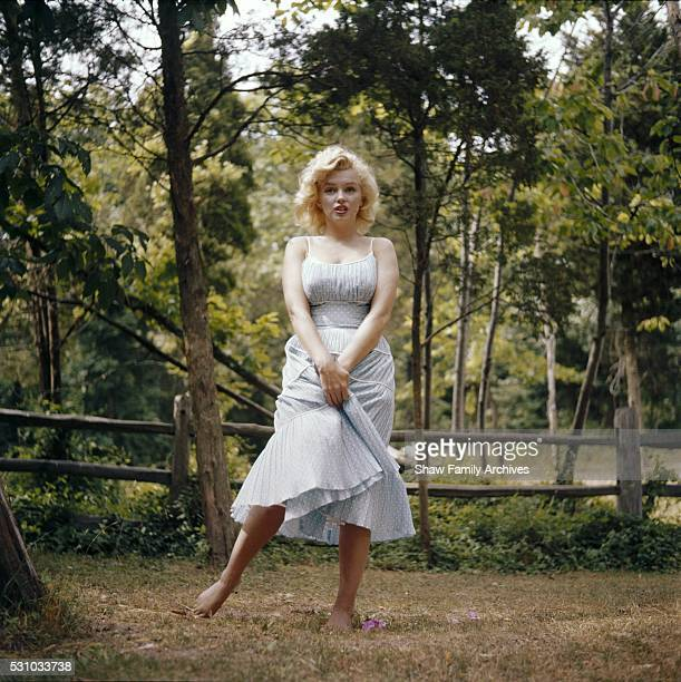 Marilyn Monroe stands barefoot wearing a blue dress in 1957 in Amagansett, New York.