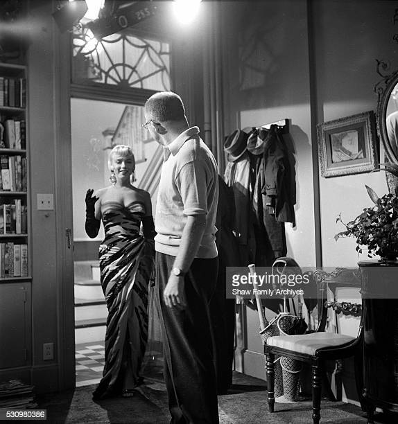 """Marilyn Monroe stands in a doorway wearing a tiger-striped dress on set with director Billy Wilder in 1954 during the filming of """"The Seven Year..."""