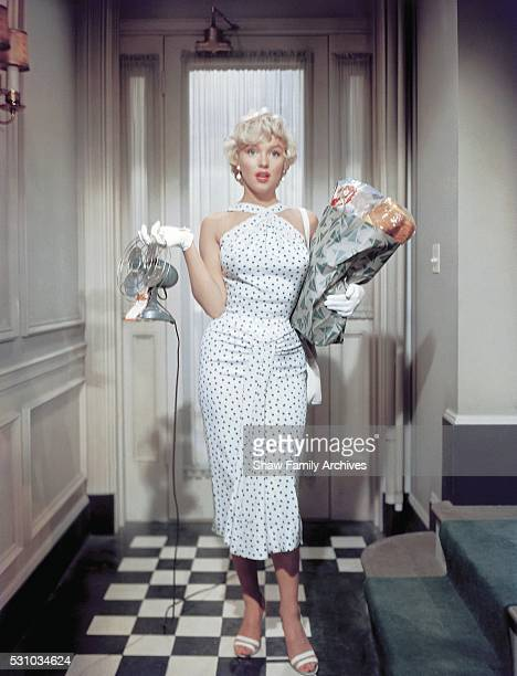 Marilyn Monroe stands in the entrance of an apartment set wearing a polkadot dress and holding groceries and a desk fan in 1954 during the filming of...