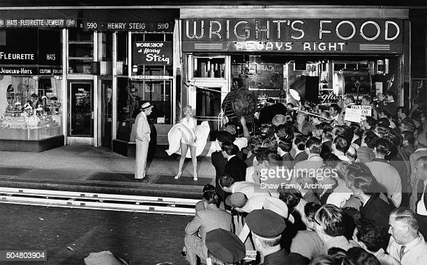 Marilyn Monroe stands over a subway grate with her white dress blowing with co-star Tom Ewell and a crowd of onlookers at the corner of 51st Street...