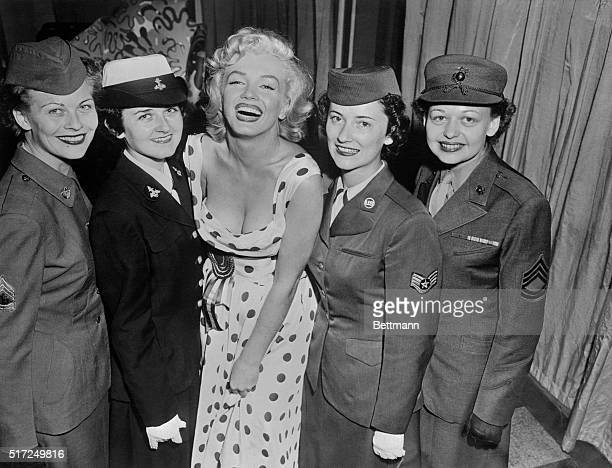 Marilyn Monroe stands with women from the US Army Navy Air Force and Marine Corps