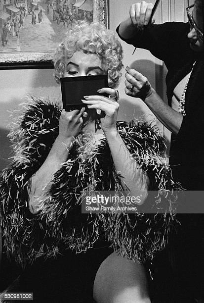 Marilyn Monroe wearing a feather boa puts on makeup to prepare for a scene during the filming of The Seven Year Itch in 1954 in Los Angeles California
