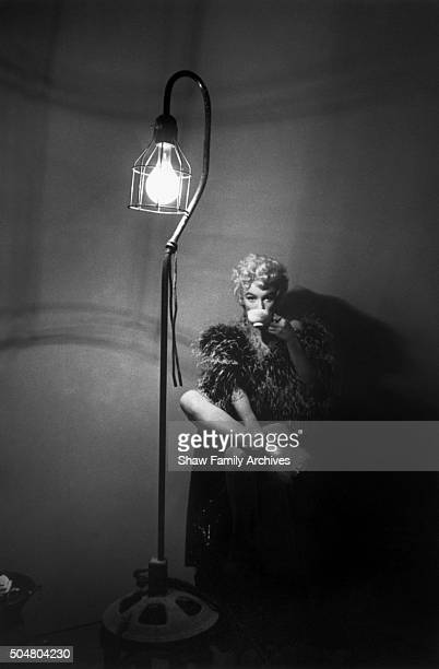 Marilyn Monroe wearing a feather boa takes a sip from a teacup next to a tall floor lamp in 1954 during the filming of 'The Seven Year Itch' in Los...