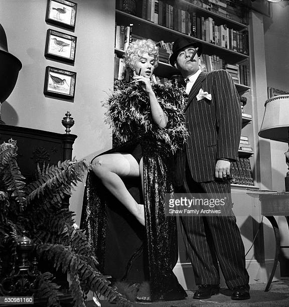 Marilyn Monroe wearing a feather boa with actor Robert Strauss during the filming of 'The Seven Year Itch' in 1954 in Los Angeles California