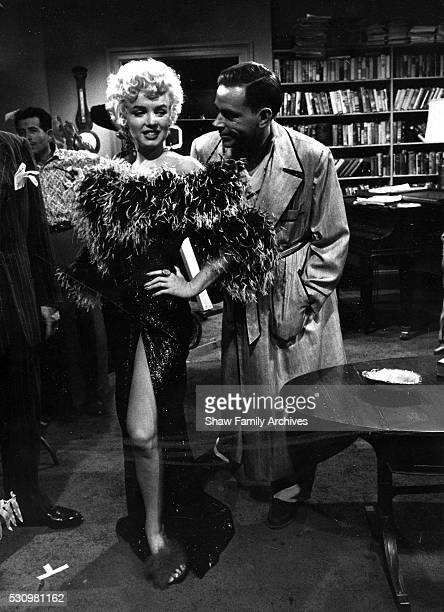 Marilyn Monroe wearing a feather boa with costar Tom Ewell during the filming of 'The Seven Year Itch' in 1954 in Los Angeles California